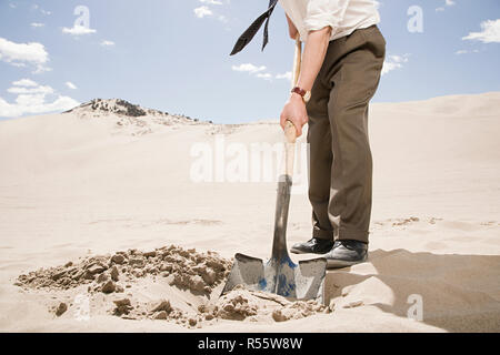 Man digging in desert - Stock Photo