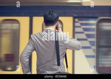 Businessman calling on phone at train station. - Stock Photo