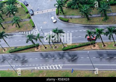 Cars drive on wet road. Raining streets, rainy day. Wet asphalt, aerial view. Malaysia. - Stock Photo
