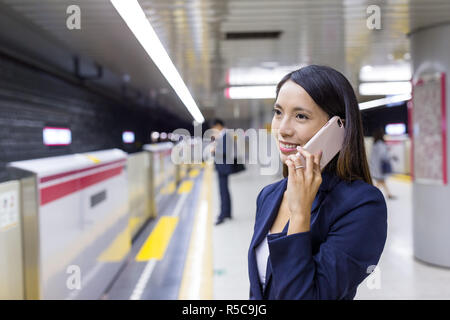 Businesswoman talk to cellphone in train station - Stock Photo