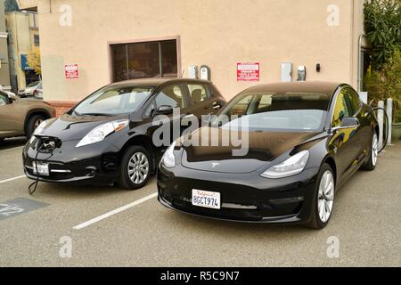 Tesla Model 3 & Nissan Leaf plug-in electric vehicles getting recharged at electric vehicle charging station, EV parking spaces in Healdsburg, CA, USA - Stock Photo