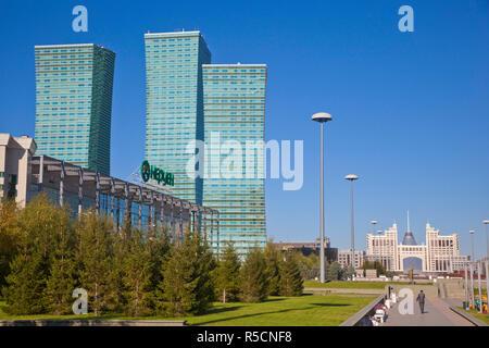 Kazakhstan, Astana, Nurzhol bulvar, central boulevard of the government and administrative zone, a business man walks towards the KazMunaiGas building - Stock Photo