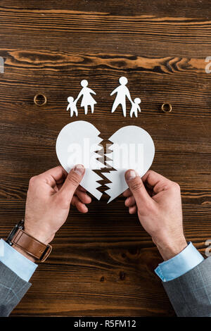cropped shot of man holding teared heart with family and engagement rings on wooden table, divorce concept - Stock Photo