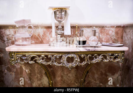 Catholic liturgical objects displayed over marble table at church. Chalice, wine and water pitcher, bell - Stock Photo
