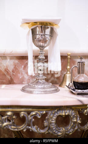 Catholic liturgical objects displayed over marble table at church. Chalice, wine pitcher and bell - Stock Photo