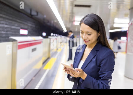 Business woman use of mobile phone in the platform - Stock Photo