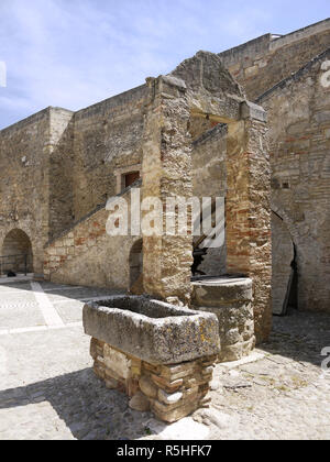 The hilltop town of Miglionico in Basilicata, Southern Italy with the Castello Malconsiglio and a water trough in the courtyard - Stock Photo