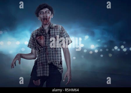 Aggressive spooky asian zombie man walking - Stock Photo