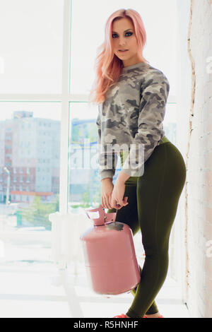 Horizontal shot of slim sporty woman has nice healthy muscular body, dressed in casual top and shorts. Athletic girl takes break after workout - Stock Photo