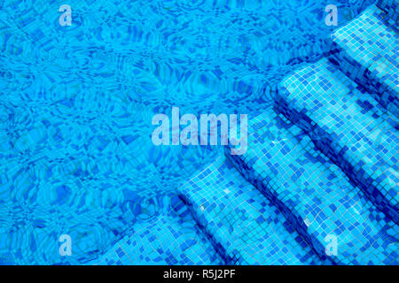 Blue steps under the water in the pool - Stock Photo