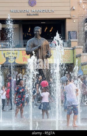 Johannesburg, South Africa, 1st December 2018. Children play in the fountain near the Nelson Mandela statue in Nelson Mandela Square in Sandton. South Africa is currently celebrating the centenary of Madiba's birth. Credit: Eva-Lotta Jansson/Alamy Live News - Stock Photo
