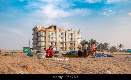 November 16,2018. Puri, Odisha, india. An Indian Conch seller selling on the Puri beach overlooking Fishermen gossiping . - Stock Photo