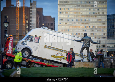 Pier Head Liverpool Waterfront promenade Bronze statue of Billy Fur, as a Morris / Austin / BMC / Leyland FG chippy van gets recovered - Stock Photo