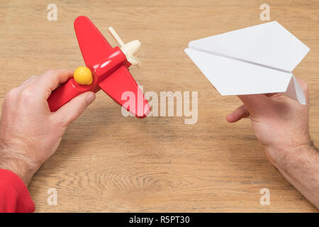 male hands play with two planes - one is paper, the second is wooden - Stock Photo