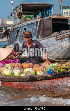 Boatman in wooden boat loaded with fruit and vegetables steers through the chaos of the Cai Rang Floating Market, Can Tho Province,Vietnam - Stock Photo