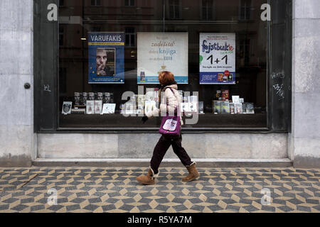 A woman walks past a bookstore promoting the book `The Global Minotaur of the former Greek Finance Minister Yanis Varoufakis in Ljubljana, Slovenia on - Stock Photo