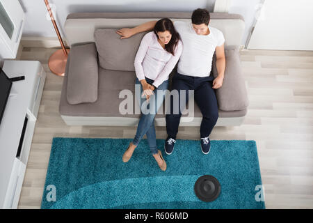 Couple Using Cleaner Robot - Stock Photo