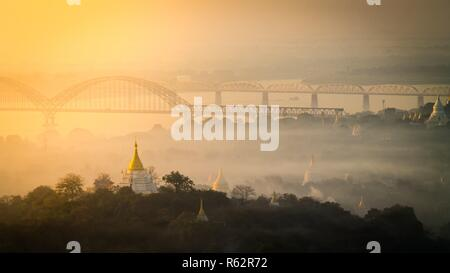 View of the river, bridges and temple pagodas at sunrise bathing in the sunlight - Stock Photo