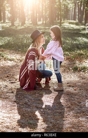 Little girl and her mother in the autumn park. Woman is wearing a stylish hat and knitted coat, girl is in pink bright sweater - Stock Photo