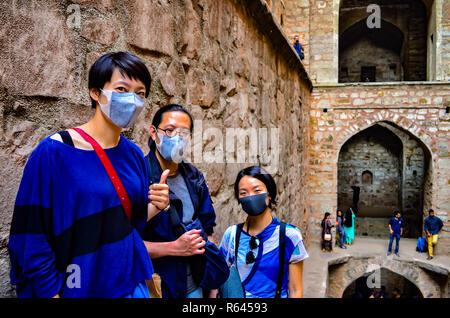 3 Asian tourists wearing masks visiting Ugrasen ki Baoli, a heritage monument in Delhi, India, Circa 2018. - Stock Photo