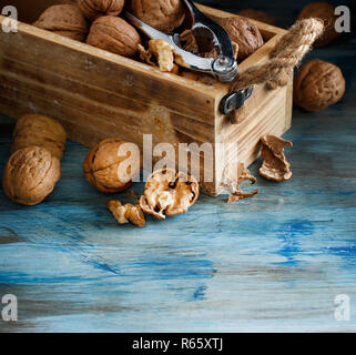 Fresh walnuts in a box on a blue wooden table - Stock Photo