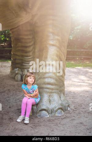 Cute little girl under huge diplodocus dinosaur - Stock Photo