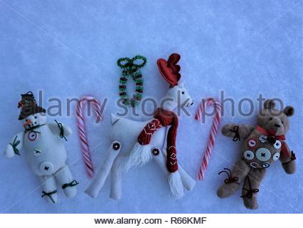 Cute trio of Christmas tree decorations with a felt teddy bear covered in buttons, snowman and reindeer, with candy canes on background of fresh snow. - Stock Photo