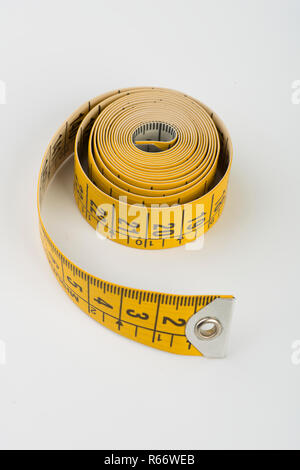 yellow tape measure for tailors on a white surface - Stock Photo