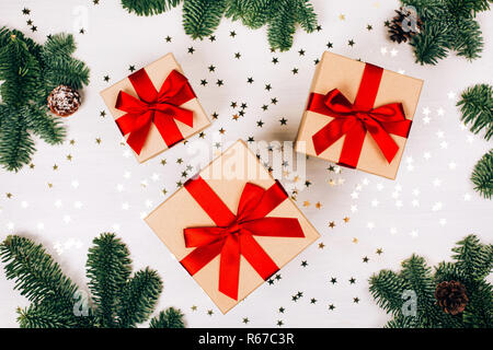Christmas presents with red ribbon on white wooden background in a frame made of fir branches with canes. Flat lay, rustic style - Stock Photo