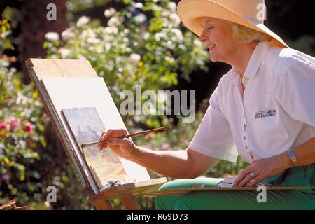 Portrait, Nahaufnahme, Frau Mitte 60 bekleidet mit gruener Hose und weissem Hemd sitzt im Garten an der Staffelei und malt - Stock Photo