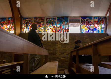 Mourners are seen in front of a stained glass window depicting Nelson Mandela as they arrive for a church service for the former South African President at Regina Mundi, Soweto, Sunday, December 8, 2013. The elder statesman died Thursday evening, December 5, 2013. PHOTO: EVA-LOTTA JANSSON - Stock Photo