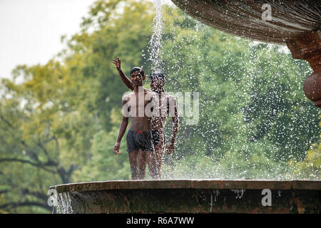 A group of boys and young men cool off in the fountain near the India Gate, a war memorial in New Delhi, India. - Stock Photo