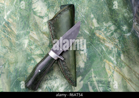 A hand forged knife and sheath displayed on top of camo fabric. - Stock Photo