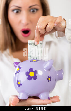 Close-up of a businesswoman hand putting money in piggy bank. Saving and financial concept. Selective focus. Focus on piggy bank, on foreground. - Stock Photo