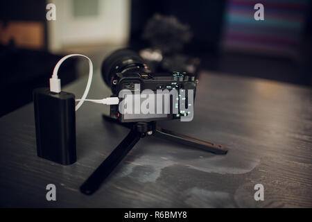 charging camera via usb on wooden table - Stock Photo