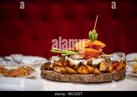 Baked potatoes with vegetables and fruits on a wooden stand, in restaurant - Stock Photo
