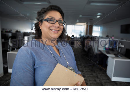 Portrait smiling, confident female manager working in call center - Stock Photo