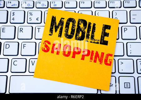 Mobile Shopping. Business concept for Cellphone online order written on sticky note paper on the white keyboard background. - Stock Photo