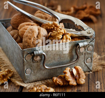 Fresh walnuts in a box on a  wooden table - Stock Photo
