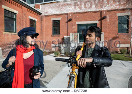 Couple with bicycle walking outside sunny brick building - Stock Photo