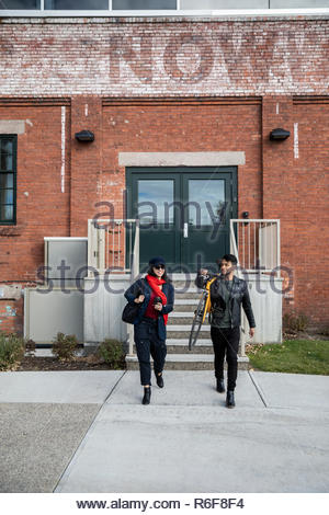 Couple with bicycle leaving brick building - Stock Photo