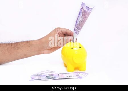 Man hand putting money in piggy bank. Isolated on the white background. - Stock Photo