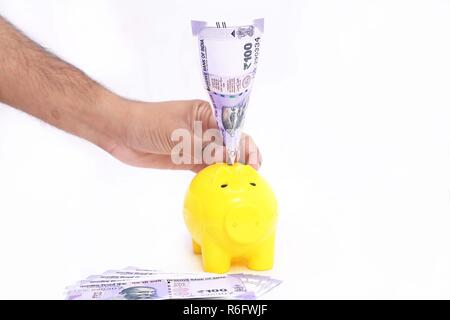 Picture of hand putting money in piggy bank. Isolated on the white background. - Stock Photo