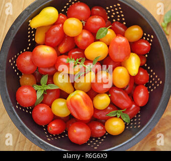 Cherry tomatoes in a dark colander - Stock Photo