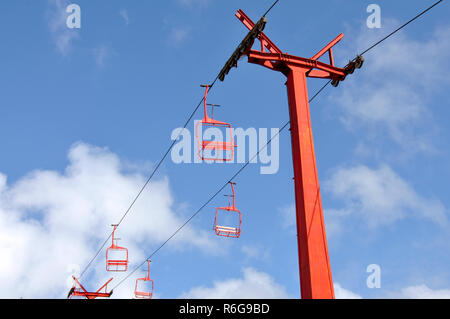 Red chairlifts in the blue sky - Stock Photo