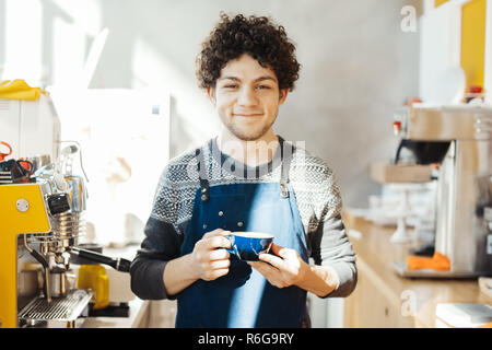 Barista smiling and holding coffee cup near bar counter in bright modern cafe. - Stock Photo