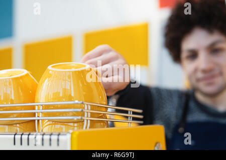 Friendly barista reaching for coffee cup and standing behind bar counter. - Stock Photo