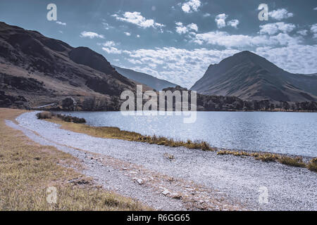 Landscape photography. Path around lake in scenic mountain valley.Hills and blue sky with clouds in background. Scenery of rural Cumbria,England. - Stock Photo