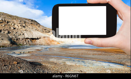 tourist photographs mud pot crater in Krysuvik - Stock Photo