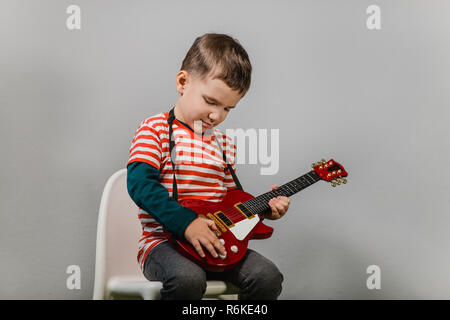 Child playing electric guitar. Portrait of young boy playing children acoustic guitar against grey background - studio shot. - Stock Photo